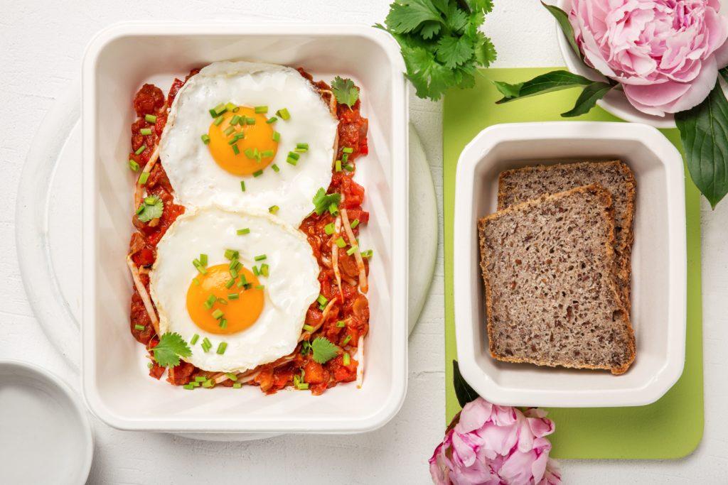 Jajka w pomidorach z papryką, kiełkami fasoli mung i kolendrą z domowych chlebem gryczanym